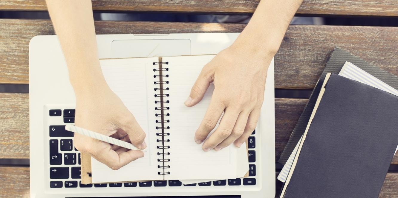 Manos escribiendo en una libreta y un ordenador